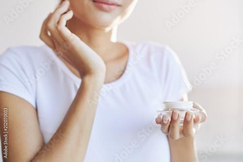 Uprawy kobieta w białej koszulce bierze opiekę skóry kładzenia śmietanka na twarzy na lekkim plamy tle