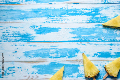 Pineapples on ice cream sticks on wooden background. Minimal summer concept. - 212073097