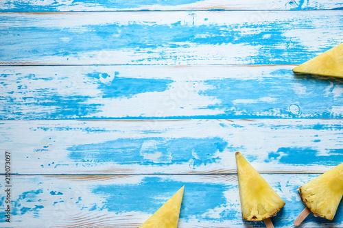 Leinwanddruck Bild Pineapples on ice cream sticks on wooden background. Minimal summer concept.