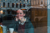 Girl with a Cup of coffee sitting in a cafe, looking at the street with reflections of the city in the window.. - 212081259