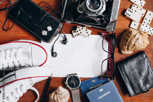 Overhead view of Traveler's accessories, Essential vacation items, Travel concept background. Different objects on wooden background.