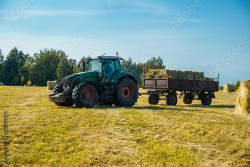 Fotobehang Trekker tractor on the field with hay