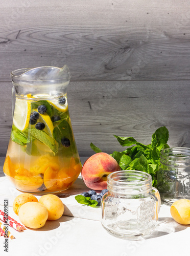 Fototapeta Lemonade of apricot, blueberry and fresh mint in jars. Summer cold drink.