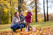 family, season and people concept - happy mother, father and little daughter with maple leaves at autumn park