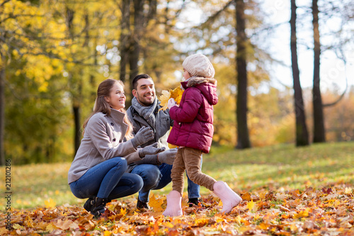 Plexiglas Hoogte schaal family, season and people concept - happy mother, father and little daughter with maple leaves at autumn park