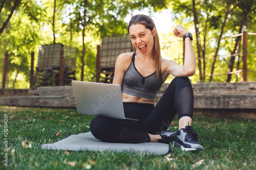 Portrait of a smiling young fitness girl using laptop - 212104209