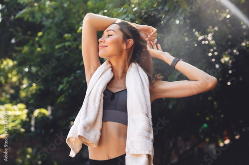 Leinwanddruck Bild Portrait of a satisfied young fitness girl standing outdoors