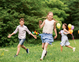 friendship, childhood, leisure and people concept - group of happy kids or friends playing tag game at birthday party in summer park - 212105258