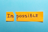 The word impossible is written on yellow paper and torn on a blue background - 212113489