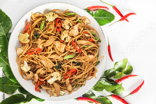 Wall mural traditional spicy asian cuisine food: wok stir fry spaghetti with fried chicken and thai spices and herbs
