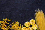 Assortment of raw pasta. Spaghetti, fusilli, penne, fettuccine on black background top view space for text - 212125633