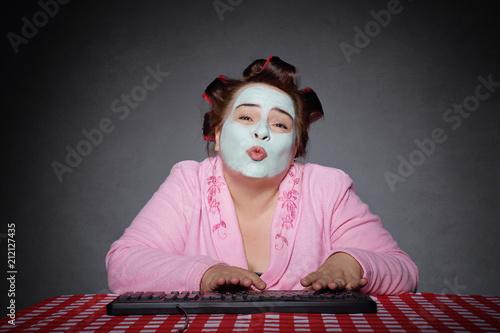 Leinwanddruck Bild femme ronde et drôle avec bigoudis tapant sur un ordinateur et faisant un baiser