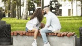 Slow motion. Couple in love kissing, sitting on a bench in a park looking each other, blurred background, side view - 212129076