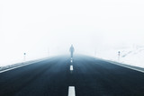 Man alone walks in the middle of the foggy asphalt road. - 212139240