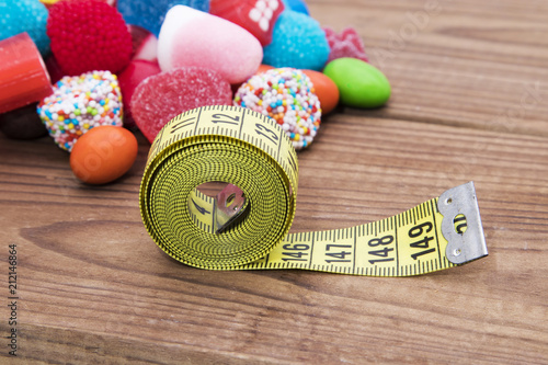 candy and candies with tape measure, concept of diet