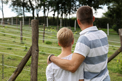 Fototapeta Father and son in vineyard. Two generations, family values. Summer holiday on farm, including kids in family business concept