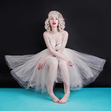 Beautiful blonde sexy woman with birthmark on face on black background. Young pale girl with blonde hair. Beautiful glamour woman in a ballet tutu with earrings on ears.