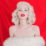 Beautiful blonde sexy woman portrait with birthmark on face in white fur coat on red background. Young pale girl with blonde hair. Beautiful woman with earrings on ears. Close-up portrait