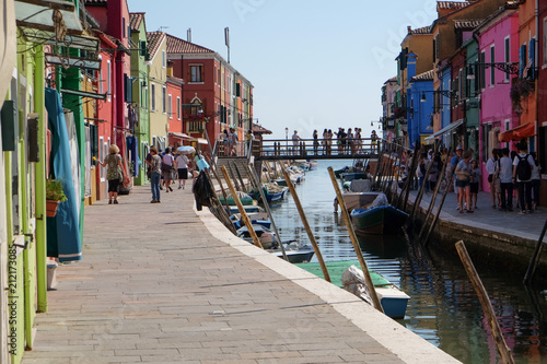 Tourists strolling alongside the canal and colorful buildings of Burano