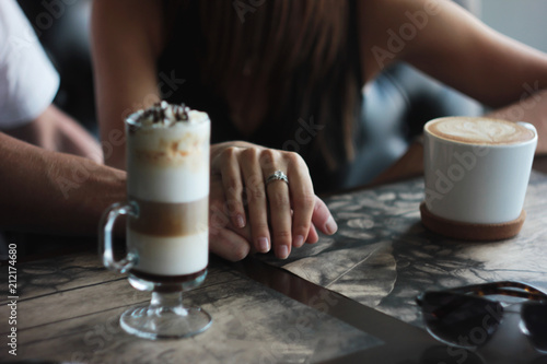 Fotobehang Chocolade Young couple on date in cafe with cappuccino latte, hand in hand