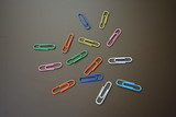 Color clips of different colors are scattered on a brown matte background - 212181415