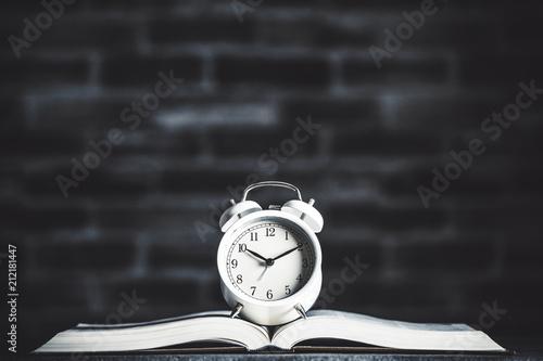 開かれた本の上にある目覚まし時計