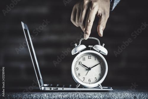 レンガ背景と目覚まし時計とパソコン