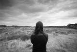 Eine einsame depressive Frau steht alleine und schaut in die Ferne. Rückansicht - 212189241