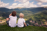 Two boys sitting on a hill and looking at the mountains. Back view - 212195856