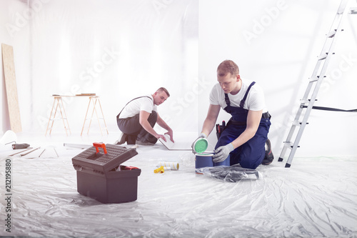 Renovation workers preparing for painting the room and installing a floor - 212195880