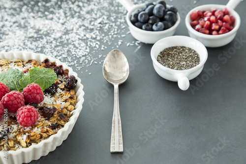 Wall mural Spoon between dessert with raspberries, linseed, pomegranate grains and berries