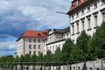 Old building with light beige decorative facade and red tiled roof behind green trees on blue cloudy sky background in berlin city germany in june 2018.