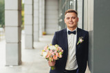 Elegant groom on a city street. In the background the projection of the columns