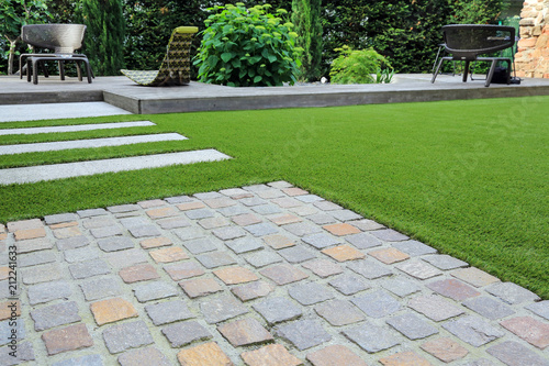 Leinwanddruck Bild Moderne Garten- und Terrassengestaltung: Materialmix aus Pflastersteinen, Betonsteinen, Holz und Kunstrasen