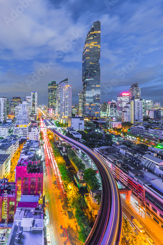 Aerial view of Bangkok City modern office buildings, condominium, hotel in Bangkok city downtown business and finance with electric sky train during twilight sky, Bangkok, Thailand. © Kalyakan