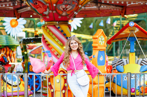 Fotobehang Amusementspark Bright summer concept. A cheerful blonde girl in pink jacket is having fun in the amusement Park. The woman looks happily at the camera and posing in front of the children's carousel with cotton candy