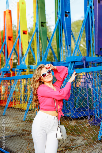 Fotobehang Graffiti Bright summer concept. A cheerful blonde girl in pink jacket and stylish sunglasses is having fun in the amusement Park. Cheerful woman smiling against bright carousel