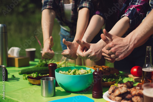Wall mural Group of friends doing thumb up signs above food table. Side view of three people showing thumbs up to picnic table full of different food. Sun shining bright.