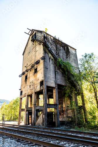 Fotobehang Oude verlaten gebouwen Abandoned retro vintage concrete loading receiving terminal building exterior in Thurmond, West Virginia ghost town with decaying structure walls, windows, railroad