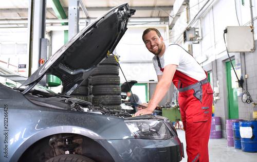 fröhlicher KFZ Mechaniker in einer Werkstatt bei der Autoreparatur // cheerful car mechanic in a workshop during car repair