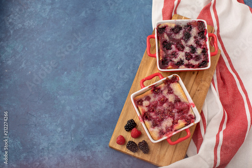Foto Murales Homemade Raspberry and Blueberry Cobblers in Red Cookware with Red and White Kitchen Towel against a Blue Background