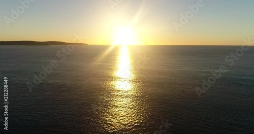 Rising hot sun over horizon of open sea from Australian continent facing Pacific ocean during aerial flying towards the Sun over calm morning water.