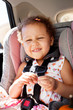 Little girl smiling in her car seat.