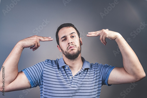 handsome young man pretending to shoot himself with his hand as a gun