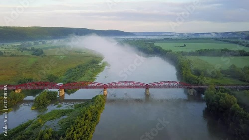Poster Bridge above river in the mist during sunrise. Natural aerial landscape at the summer time