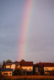 Rainbow in the sky above the houses. - 212322072