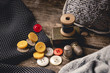 Leinwanddruck Bild - Close-up of wooden sewing spool and buttons set on wooden table