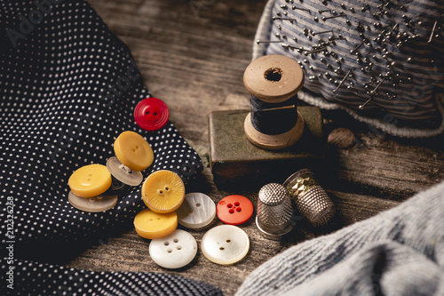 Leinwanddruck Bild Close-up of wooden sewing spool and buttons set on wooden table