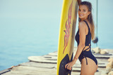 Young sexy woman with surf board on the beach, ready for surfing. Waving hand. Positive emotions. Close up - 212327051