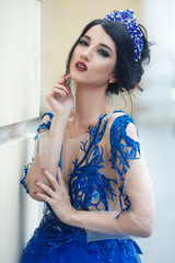 Portrait of a beautiful brunette girl with a crown on an elegant hairstyle and blue make-up in the color of a lace dress. © ksi
